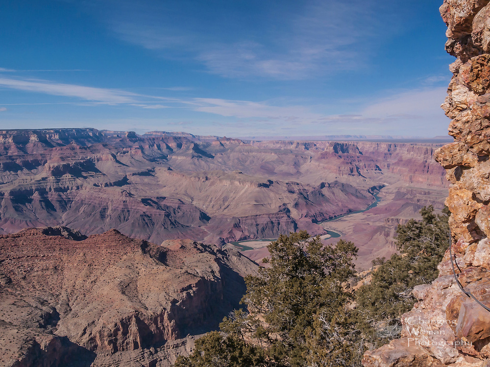 Standing at the base of Desert View Watchtower's western side, with the tower's base framing the image's right side, one sees the Colorado River's upstream channel winding east toward the distant Painted Desert.  The high plateau of Grand Canyon's North Rim defines the horizon at the image's left side: this is the Walhalla Plateau, and the Jupiter, Venus, and Apollo Temples lie between it and the grand curve of the Colorad near the image's center.