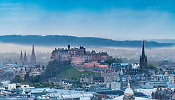 View of floodlit Edinburgh Castle in the evening from Salisbury Crags in Edinburgh, Scotland, United Kingdom.