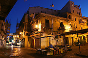 By 6:00 a.m., the fruit seller across the cobbled street from the Manzos' third-floor walk-up has already arranged half of his display. Living in the heart of Palermo, Sicily's ancient Capo Market, the family is constantly enveloped in the cry and clamor of commerce; and, recently, the clatter of restoration work (scaffolding at the end of street around market gates). To Giuseppe, who grew up in this same Italian neighborhood, the hubbub is the sound of home. Hungry Planet: What the World Eats (p. 177).