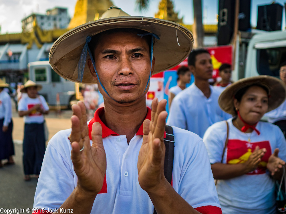 06 NOVEMBER 2015 - YANGON, MYANMAR: A man applauds the speakers at the final NDF election rally of the 2015 election. The rally was held in central Yangon, next to the historic Sule Pagoda and across the street from Yangon city hall. The National Democratic Force (NDF) was formed by former members of the National League for Democracy (NLD) who chose to contest the 2010 general election in Myanmar because the NLD boycotted that election. There have been mass defections from the NFD this year because many of the people who joined the NFD in 2010 have gone back to the NLD, which is contesting this year's election and widely expected to win it. Campaigning in the Myanmar election ended Friday. People go to the polls Sunday.     PHOTO BY JACK KURTZ