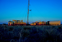 Large transport trucks parked at an onshore drilling operation site