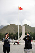 Tibetan women pray in front of the Potala, while a nearby Chinese flag waves in the wind.