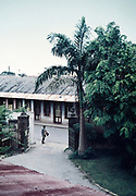 Captioned as 'View of exit gate on a sunny morning - see postman' , Trinidad early 1960s