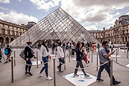 The entrance of the Louvre Museum in Paris with people waiting to enter. The line is shorter than ever.