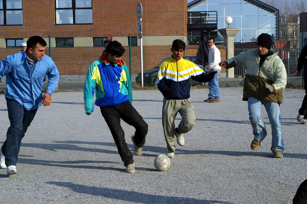 A group of refugees having a kick around with a football during the day in Calais, France..After the Sangatte refugee camp closed down an average of 200 refugees lived on the streets of Calais, without food, money or accommodation, trying most nights to get to Britain.  There were many different nationalities, mainly Iraqi and Afghani, but also Sudanese, Palestinian and Turkish. 95% are male, aged between 16 and 50.
