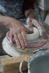 Close-up of female potter moulding clay in workshop, Bavaria, Germany