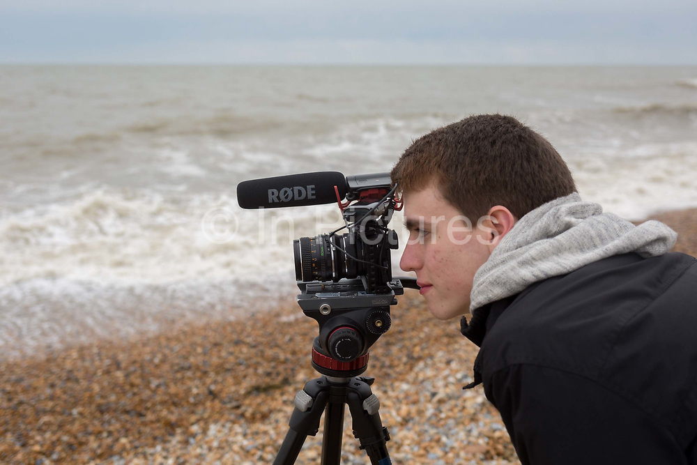 A teenage student from college in London looks through the viewfinder of a camera to learn the art of film production on location at the south coast, on 30th April 2017, at Winchelsea, England.