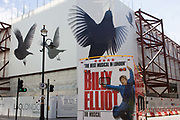 A bus advert for the musical Billy Elliott drives past a construction hoarding featuring giant birds in flight spreading wings. As the bus swings right, turning away from this street corner near Leicester Square, we see the character Billy leaping in the air as, in the story of a working class boy during the 1980s minor's strike, becomes a student of ballet, he dances his way to a different future. The large birds behind echo his flight and outstretched arms.