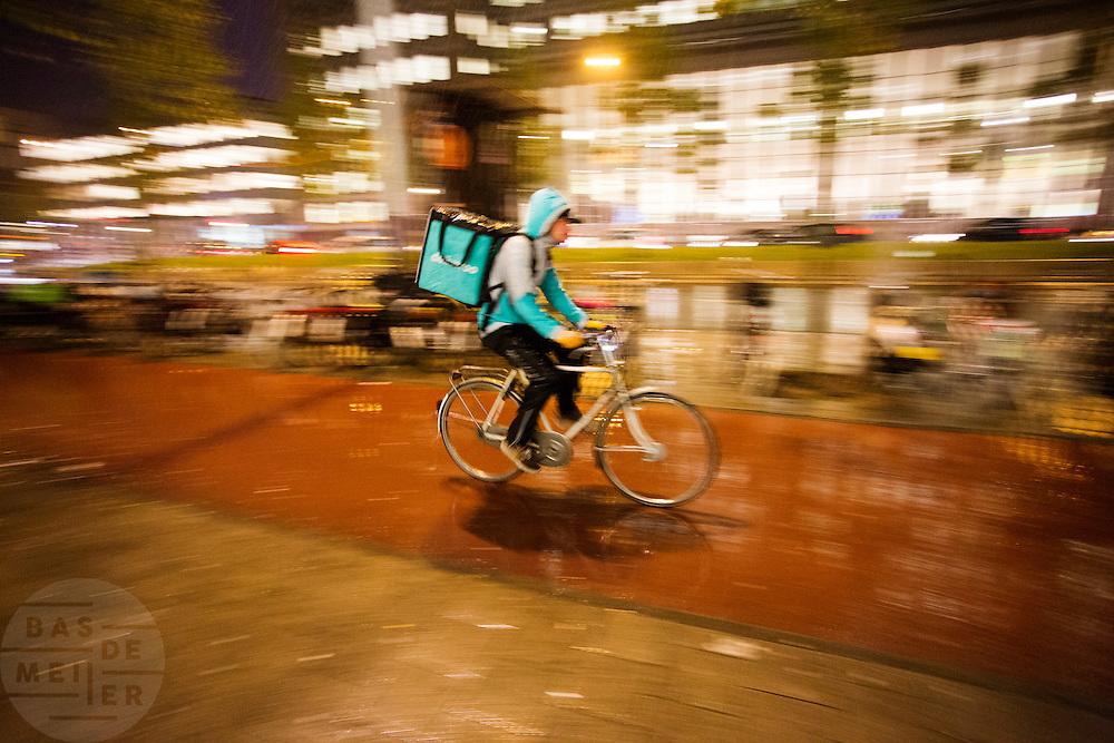 In Amsterdam rijdt een bezorger van fietsbezorgdienst Deliveroo door de stromende regen.<br /> <br /> A messenger of Deliveroo is riding in the rain in Amsterdam.
