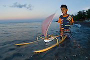 Young boy in Tulamben, Bali, Indonesia playing in the surf with a model or toy jukung, the traditional fishing vessel in Bali. Image available as a premium quality aluminum print ready to hang.
