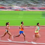 TOKYO, JAPAN August 7:   Sifan Hassan of the Netherlands (orange shirt) poised to make her move while winning the gold medal in the  10000m final for women from Kalkidan Gezahegne of Bahrain and Letesenbet Gidey of Ethiopia during the Track and Field competition at the Olympic Stadium  at the Tokyo 2020 Summer Olympic Games on August 7th, 2021 in Tokyo, Japan. (Photo by Tim Clayton/Corbis via Getty Images)