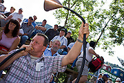 29 JULY 2007 -- BRUNIG, OBWALDNER, SWITZERLAND: A spectator blows a home made horn during the Brunig Schwinget, a wrestling tournament in Brunig, in the canton of Obwaldner, Switzerland. Schwingets are Swiss style wrestling tournaments held throughout Switzerland. They are usually held outdoors in Alpine mountain passes. Wrestlers wear special canvas pants over their regular clothes. They grip each others pants and wrestle on bed of sawdust. The Schwinget in Brunig is one of the most popular in Switzerland with over 6,000 spectators and more than 120 wrestlers. There is Swiss Alpenhorn blowing, flag throwing and yodeling at the Schwinget.  Photo by Jack Kurtz