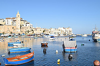 Marsaskala harbour with boats and dishing vessels and church in the distance