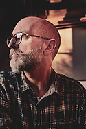 Sitting portrait of the photographer a middle aged male wearing spectacles with a beard