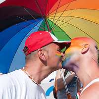 Participants of the Gay Pride March kiss each other under a rainbow colored umbrella in Budapest, Hungary on June 18, 2011. ATTILA VOLGYI