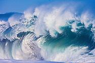 Huge powerful wave breaking off a Kauai, Hawaii beach