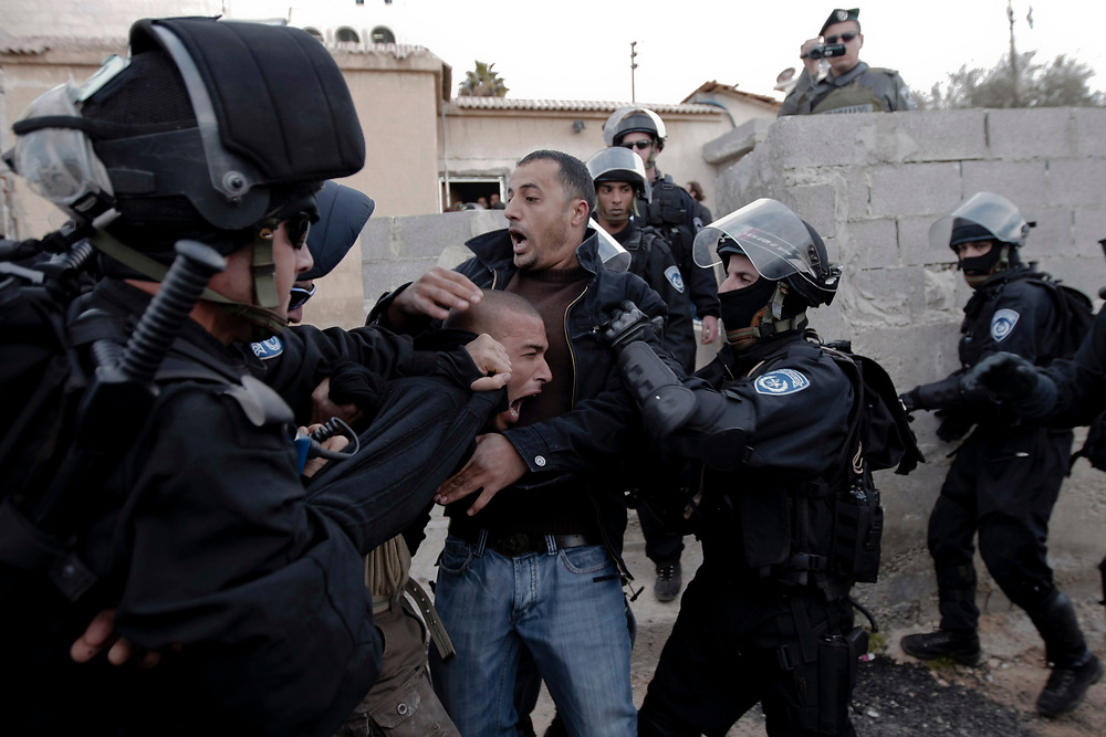 A Palestinian man is detained by Israeli police officers while contractors working for the Israeli police department seal off entrances to the house (unseen) of a Palestinian man who attacked Mercaz Harav Yeshiva, a Jewish religious seminary in March of last year killing eight people, in east Jerusalem, on January 19, 2009.