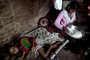 (name changed) Neelam Bharadwaj, 16, (right) is preparing some rice for cooking while sitting inside her family's home in Rajbhar village, located around 20 kilometres away from Varanasi, in Uttar Pradesh, India. Neelam was raped when she was 13 years old. After walking to a local shop on the main road neighbouring her village, she was forcibly picked up by two men. While one of them was raping her in the bushes, the other watched out. After some time, she managed to free herself and run away, hiding under a bridge in cold dirty water for several hours. When she returned home in the morning, the family was too afraid to go to the police, but activist Mangla Parsad, 34, from PVCHR, convinced the family to take the right action. The police initially insulted and threatened the family for bringing the facts up, but filed the official case (FIR) nevertheless. The rape was not mentioned in the file due to an inaccurate and superficial medical record that did not, in fact, mention it. Because of social shame facing by victims of rape in India, the family agreed to wed Neelam to an older man, with help of an agent. After the marriage, her husband raped her again for a whole month before she decided to return home with her family. Neelam's father works in the metal industry in Mumbai and manages to send around 2-3000 INR every month. He only visits the family once in a year. Neelam goes to school and she is studying in 11th Class Standard. She is interested in doing BA in Arts after completing her high school 12th final year.