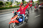 """Mar. 27, 2010 - BANGKOK, THAILAND:  A Red Shirt demonstrator rides his motor scooter through Bangkok Saturday March 27. More than 80,000 members of the United Front of Democracy Against Dictatorship (UDD), also known as the """"Red Shirts"""" and their supporters marched through central Bangkok March 27 during a series of protests against and demand the resignation of current Thai Prime Minister Abhisit Vejjajiva and his government. The protest is a continuation of protests the Red Shirts have been holding across Thailand. They support former Prime Minister Thaksin Shinawatra, who was deposed in a coup in 2006 and went into exile rather than go to prison after being convicted on corruption charges. Thaksin is still enormously popular in rural Thailand.    PHOTO BY JACK KURTZ"""