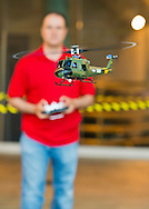 JOHN AKIOS, of Bellmore, is flying a Huey UH-1 Helicopter remote control model, with collective pitch like a real helicopter, at the 8th Annual Flying Model Show sponsored by Academy of Model Aeronautics (AMA) and Model Airplane Clubs of Nassau, Suffolk & Queens, in the lobby of the Cradle of Aviation Museum.