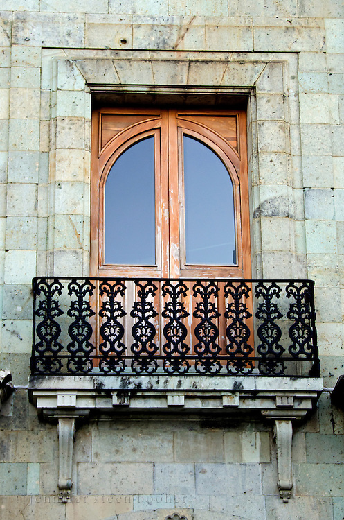 A tall french door opens onto a graceful wrought iron balcony at the Museo del Palacio, Oaxaca, Mexico