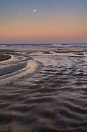 Moonset at dawn over Little Morro Creek from Morro Strand State Beach, Morro Bay, California