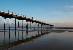 © Licensed to London News Pictures. <br /> 09/10/2014. <br /> <br /> Saltburn, United Kingdom<br /> <br /> A man stands on the pier watching the sunrise in Saltburn by the Sea in Cleveland.<br /> <br /> Photo credit : Ian Forsyth/LNP