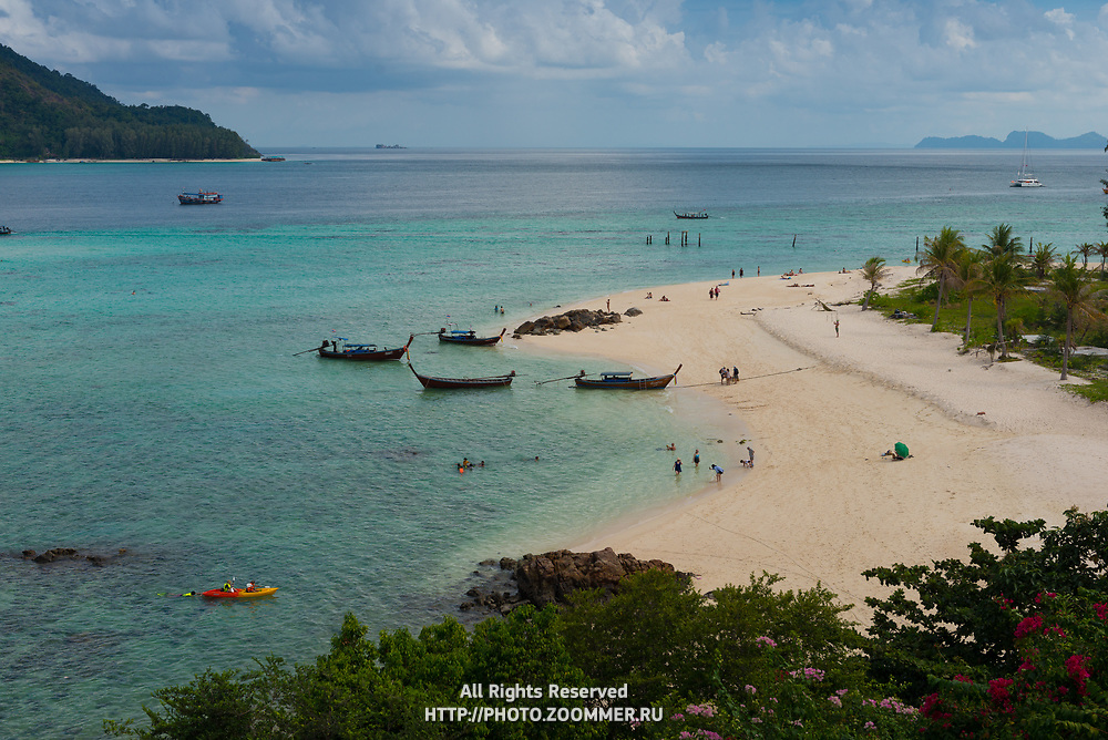 Aerial view of Ko Lipe Sunrise beach with longtail boats and kayaks, Thailand