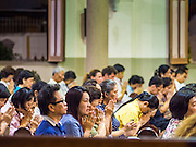 18 FEBRUARY 2015 - BANGKOK, THAILAND: People in Santa Cruz Catholic Church for a weekday evening mass in the Kudeejeen neighborhood in Bangkok. Santa Cruz church was established in 1770 and is the heart of the community. It is one of the oldest and most historic Catholic churches in Thailand. The church was originally built by Portuguese soldiers allied with King Taksin the Great. Taksin authorized the church as a thanks to the Portuguese who assisted the Siamese during the war with Burma. Most of the Catholics in the neighborhood trace their family roots to the original Portuguese soldiers who married Siamese (Thai) women. There are about 300,000 Catholics in Thailand in about 430 Catholic parishes and about 660 Catholic priests in Thailand. Thais are tolerant of other religions and although Thailand is officially Buddhist, Catholics are allowed to freely practice and people who convert to Catholicism are not discriminated against.            PHOTO BY JACK KURTZ