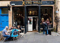 Exterior view of people in The Wall cafe on Cockburn Street in Edinburgh Old Town, Scotland, UK