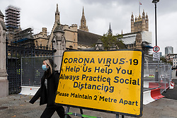 © Licensed to London News Pictures. 15/10/2020. LONDON, UK. A woman wearing a facemask walks by a coronavirus alert sign outside the Houses of Parliament in Westminster.  Currently, England alert level : Tier 1, Medium (the rule of six applies indoors and outdoors, pubs and restaurants shut at 10pm) applies, but to try to further control the coronavirus pandemic, the UK government has announced today that from Saturday the capital, as well as other regions in the UK, will move to the more stringent England alert level :Tier 2, High (no households mixing indoors, the rule of six applies outdoors, pubs and restaurants shut at 10pm).  Photo credit: Stephen Chung/LNP