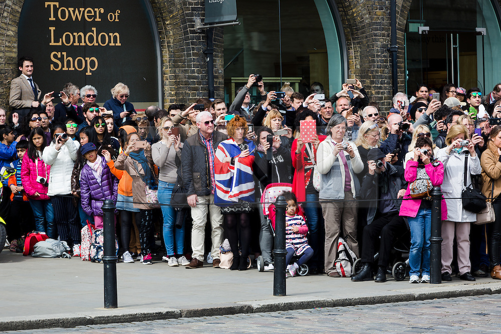 © Licensed to London News Pictures. 21/04/2016. London, UK. Crowds of people watch the Honourable Artillery Company (HAC) fire a 62 round gun salute at The Tower of London, near Tower Bridge to mark the 90th birthday of Great Britain's Queen Elizabeth II. A Royal Salute normally comprises 21 guns, but is increased to 41 if fired from a Royal Park or Residence and uniquely, at The Tower of London, a total of 62rounds are fired on Royal anniversaries, including an additional 21 guns for the citizens of the City of London to show loyalty to the Monarch.  Photo credit : Vickie Flores/LNP