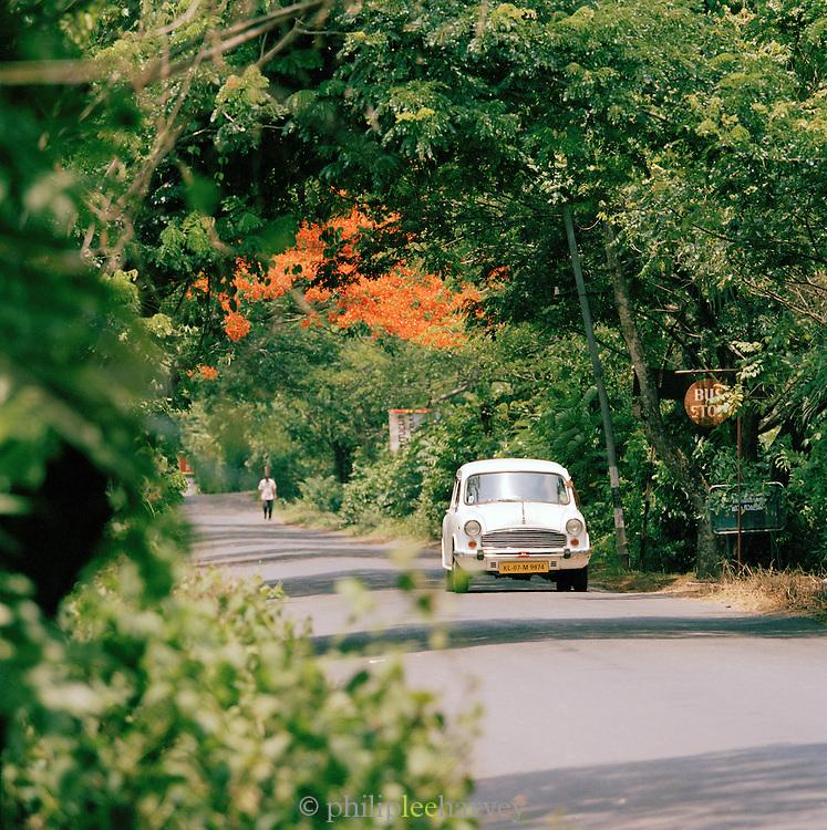 Ambassador car driving along a road, Kerala, India