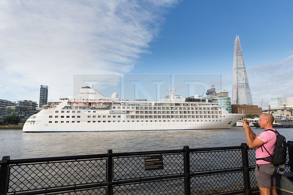 © Licensed to London News Pictures. 01/08/2017. LONDON, UK.  A man photographs Silver Wind, a huge 514 feet long, 17,400 ton cruise liner as she leaves London passing the Shard before travelling under Tower Bridge this morning after a brief visit, towed backwards by two tugs. Silver Wind carries just 296 passengers and its owner, Silversea claim that the ship has amongst the highest space-to-guest ratios in the cruise ship industry, with the largest suites measuring 1,314 square feet. Tickets cost thousands of pounds, but all guest expenses, even champagne are included in the price. Environmentalists claim the pollution created by giant cruise ships outweigh their economic benefits. The Port of London Authority (PLA) are conducting a work programme during 2017 to monitor air quality and pollution caused by river traffic on the River Thames.  Photo credit: Vickie Flores/LNP