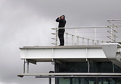 © Licensed to London News Pictures. 12/09/2019. London, UK. A police officer uses binoculars to look out from the roof of Terminal 5 at Heathrow Airport in West London where activists from Heathrow Pause, a splinter of the environmental protest group Extinction Rebellion, are planning to fly toy drones early tomorrow morning in an attempt to cause disruption. Photo credit: Ben Cawthra/LNP
