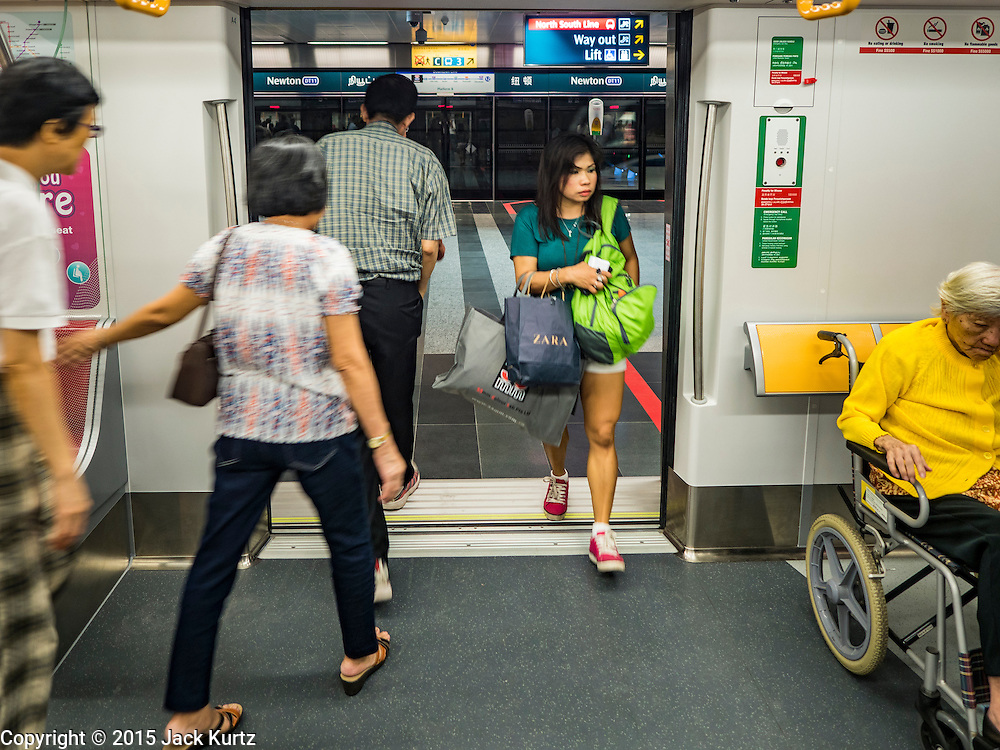"""27 DECEMBER 2015 - SINGAPORE, SINGAPORE:  Passengers get off and on the expanded Downtown Line on the first day of service on the new line. Singapore opened the extension of the Downtown Line on its subway system Sunday. The extension is a part of Singapore's plans to make the city-state a """"car lite"""" metropolis with plans to double the current subway to more than 360 kilometers of track by 2030. The government plans to have 80% of homes within a 10 minute walk of a subway station.   PHOTO BY JACK KURTZ"""
