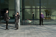The financial district. The city of London. Smokers on their mobile phones outside their office building. London, UK.