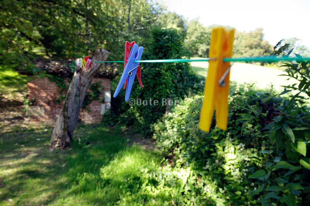 empty washing line with various colored clothespins in a backyard
