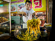 20 OCTOBER 2017 - BANGKOK, THAILAND: A noodle seller tosses fried noodles on the first day of the Vegetarian Festival, what Thais call the Taoist Nine Emperor Gods Festival, in the Chinatown neighborhood of Bangkok, Thailand. It is a nine-day Taoist celebration beginning on the eve of 9th lunar month of the Chinese calendar. For nine days people participating in the festival wear only white and don't eat meat, poultry, seafood, and dairy products. The vegetarian festival is celebrated throughout Thailand, but especially in Phuket and Bangkok, cities with large ethnic Chinese communities.       PHOTO BY JACK KURTZ