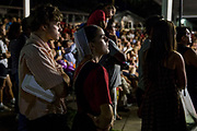 WASHINGTON, USA - August 19: Two Amish teens watch a hypnotist try to get volunteers from the crowd to do things during a comedy show at the Montgomery County Agricultural Fair in Gaithersburg, Md., USA on August 19, 2017. The Amish are a fundamental people that typically shun technology but agricultural fairs bring people together from many different backgrounds.