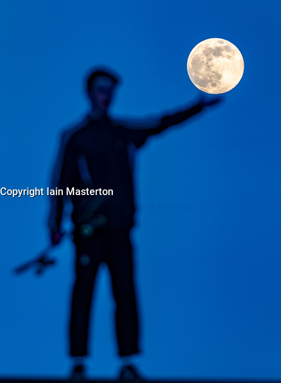 Edinburgh, Scotland, UK. 7 April 2020. Supermoon as seen from Calton Hill in Edinburgh. Tonight the full Moon is at perigee — the closest point in the Moon's orbit to Earth, making it appear bigger and brighter in the sky. Pictured. Young man appears to hold the Supermoon. Iain Masterton/Alamy Live News
