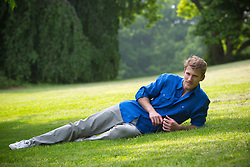 handsome man with blond hair relaxing on a green lawn