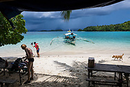 A bangka boat is parked at Paradise Island, one of several stops in a day-long boat tour out of Port Barton, Palawan, Philippines. Two passengers from Spain are on the beach.<br /><br />(July 7, 2019)