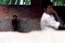Tamil Nadu, INDIA. March1994..A man who has his hands and feet in chains is standing close to the wall which is covered with words/phrases..This is the fate awaiting those, who the locals believe are possessed by evil spirits.