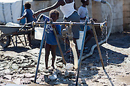 Child getting water provided in a tent city in Port-au-Prince that is untreated. The lack of clean water makes Haiti ripe for the spread of cholera.  Since the earthquake on January 12, 2010, thousands still live in tent cities that lack sanitation.