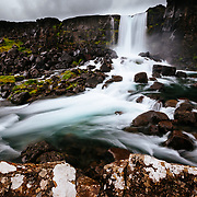 Oxararfoss falls flows over boulders between American and Eurasian techtonic plates in Þingvellir National Park in Iceland.