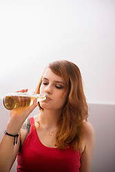 Young red-haired woman drinking beer from the bottle, Munich, Bavaria, Germany