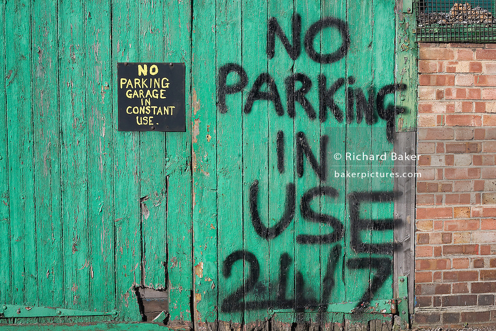 A No Parking sign painted on to a garage door tells car drivers this entrance is in constant use 24/7 in Loughborough Junction, South London..
