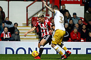 Sergi Canos of Brentford (L) takes on Daniel Pudill of Sheffield Wednesday (R). EFL Skybet football league championship match, Brentford v Sheffield Wednesday at Griffin Park in London on Saturday 30th December 2017.<br /> pic by Steffan Bowen, Andrew Orchard sports photography.