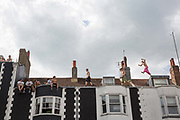 A group of young men scale the roof tops along London Road during the Brighton Pride parade and carnival on the 4th August 2018 in Brighton in the United Kingdom. Brighton Pride is an annual event held in the city of Brighton and Hove, England, organised by Brighton Pride, a community interest company who promote equality and diversity, and advance education to eliminate discrimination against the lesbian, gay, bisexual and transgender community.